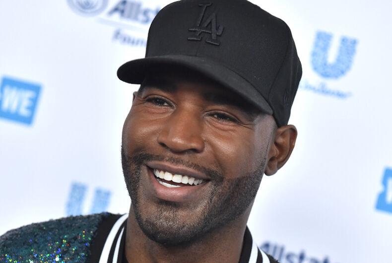 Karamo Brown, a black man with facial scruff, smiles while wearing a black baseball cap.