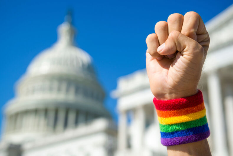 Hand wearing gay pride rainbow wristband making a power fist gesture in front of the US Capitol Building in Washington, DC, USA