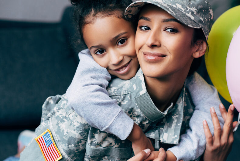 African american daughter hugging her mother in military uniform with balloons at home