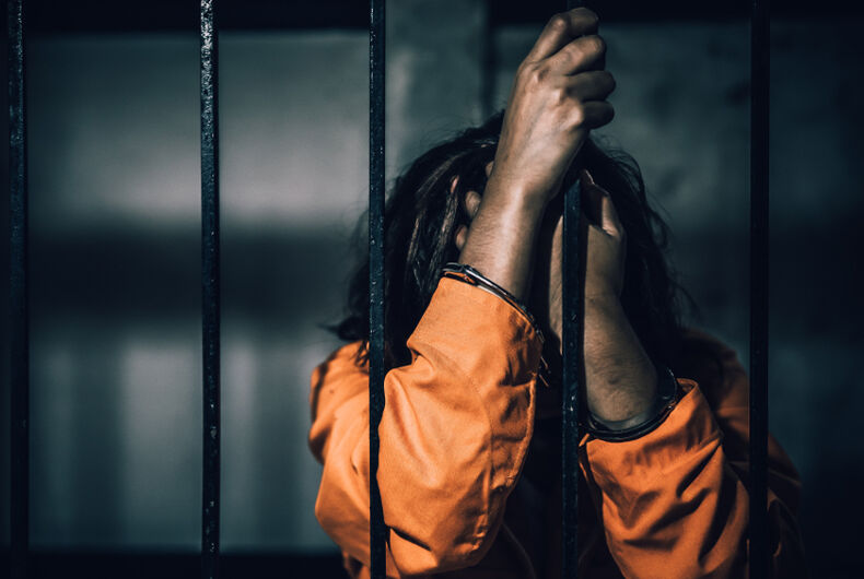 A woman holds onto the bars of her prison cell while wearing an orange jumpsuit.