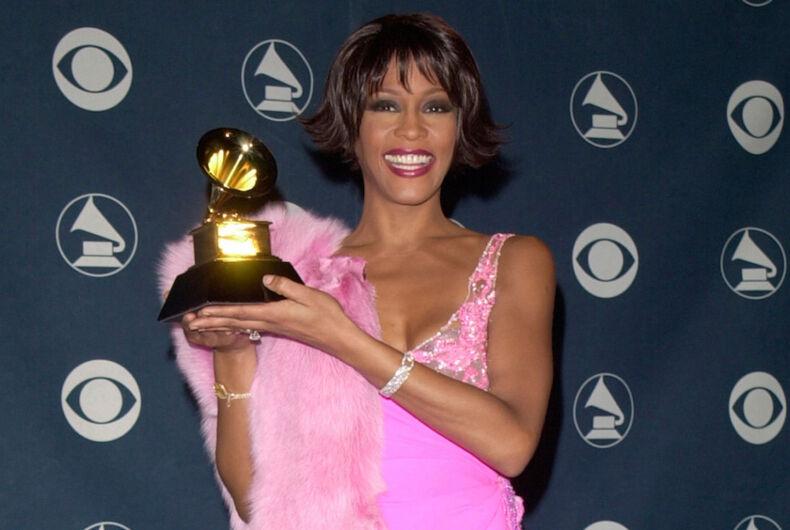 Whitney Houston holds up a Grammy Award. She's wearing a pink dress.