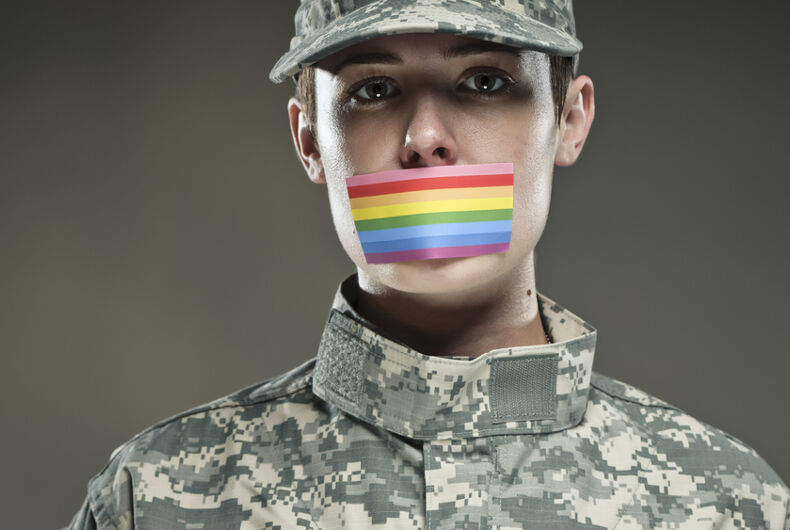 A soldier has a rainbow flag sticker covering their mouth.