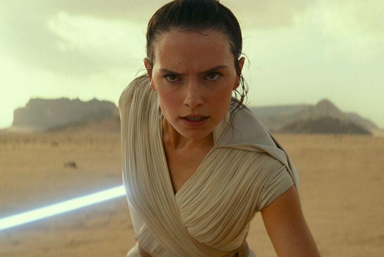 A woman running in a desert with a light saber