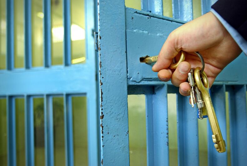 Guard turning keys to a jail cell