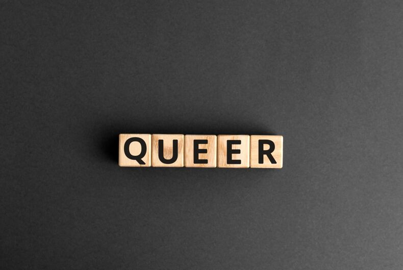 Queer - word from wooden blocks with letters, queer concept, random letters around, top view gray background
