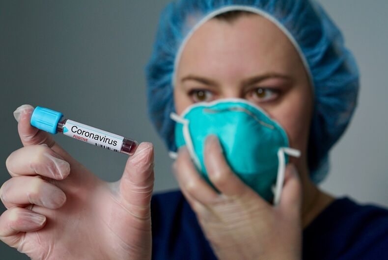 A doctor with a mask holding a vial labeled