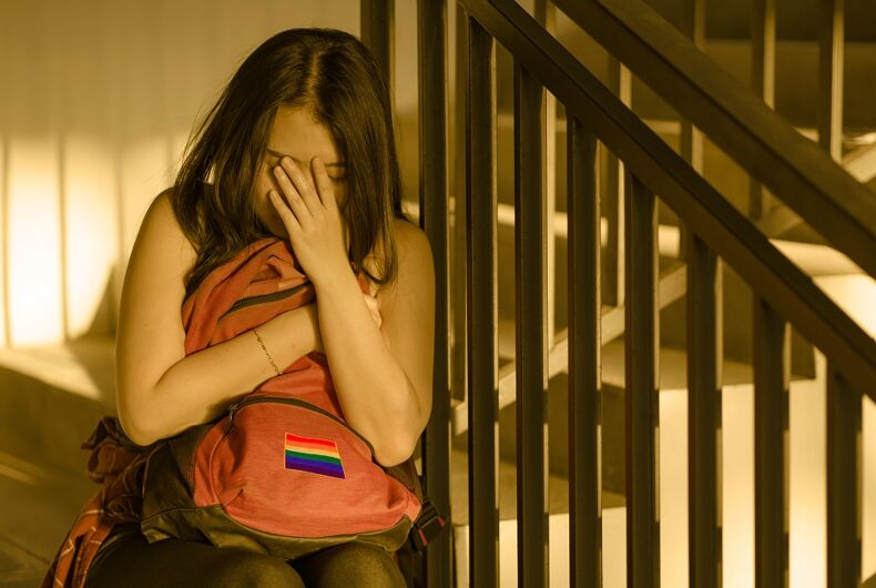 A teen holding a backpack with a rainbow on it. She's crying, maybe because her foster parents are sending her to conversion therapy.