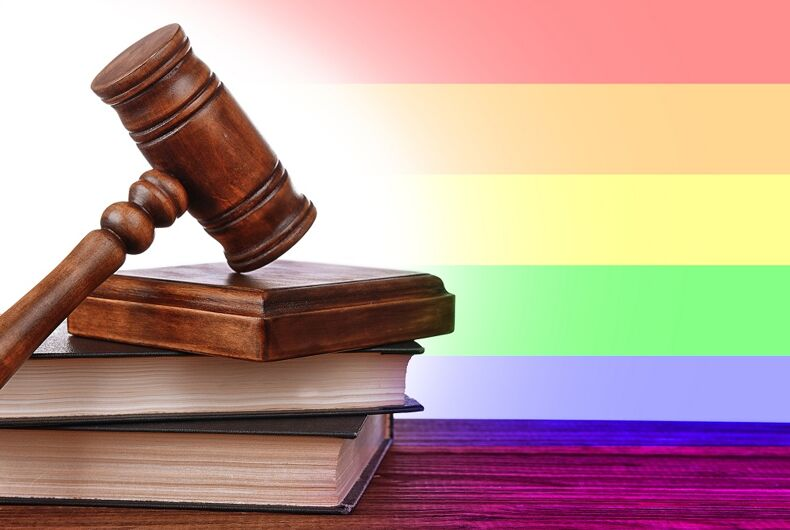 A gavel in front of a rainbow flag