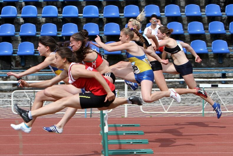 High school girls jumping over a hurdle at a track meet