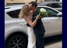 Lesbian couple gets married in the street as guests watch from parked cars & sidewalks