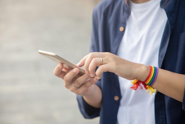 modern LGBT woman with ribbon symbol using smartphone