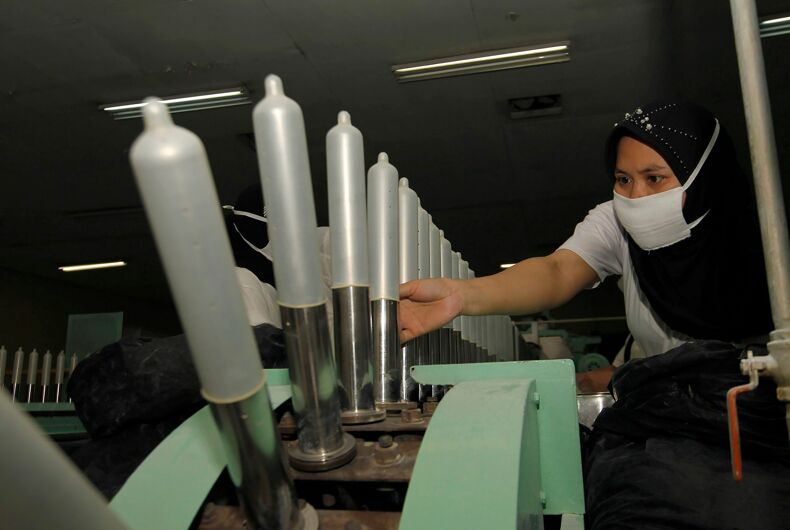 A worker inspects finished condoms at a factory in Bandung, Indonesia.