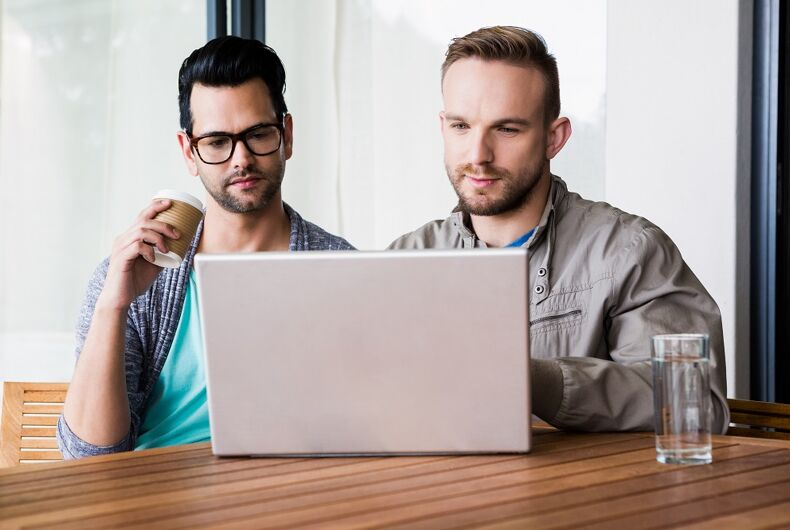 A gay couple looking at a computer. They are not smiling.