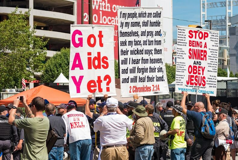 Protestors with anti-LGBTQ signs. One says
