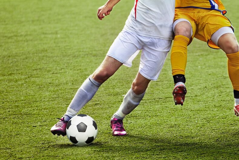 Two soccer players kicking a ball