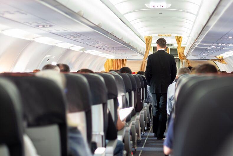 Flight attendant walking down an aisle