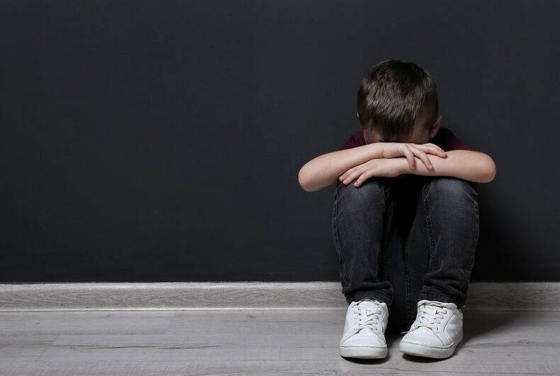 A sad kid. Could be because of consersion therapy or maybe it's because the kid's parents are making them pose for stock photos.