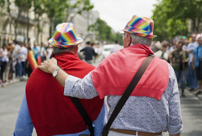 An elderly gay couple in rainbow hats