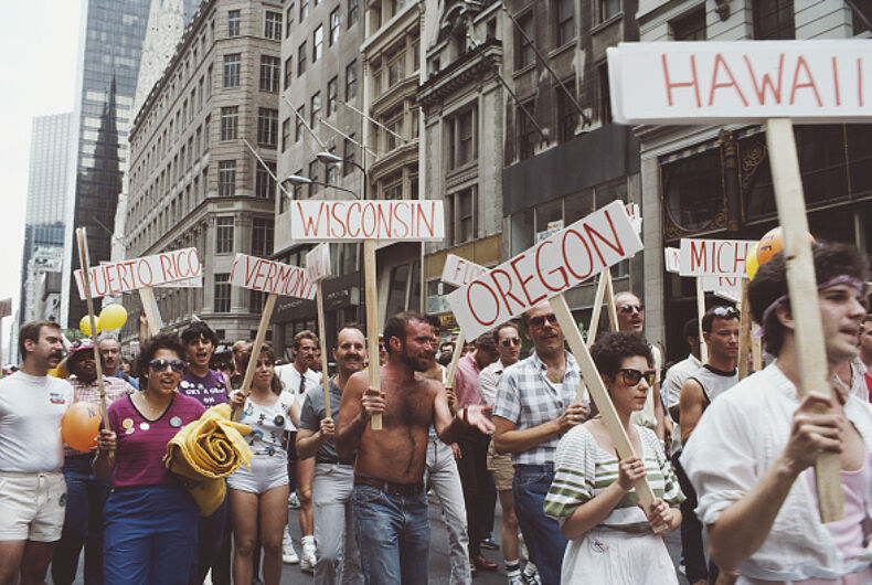 Men and women carry signs during the Gay Pride parade in New York City, June 1984.