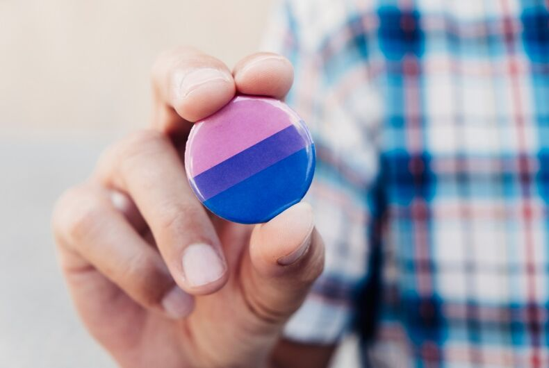 A man holding a pin with the bisexual pride flag on it