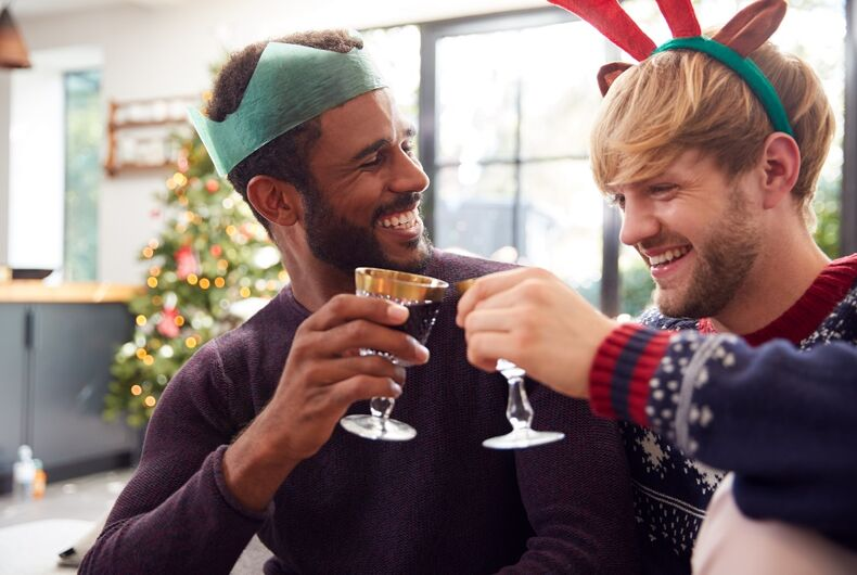 Two men dressed in Christmas attire share wine and they look like a couple. The image is not from the film.