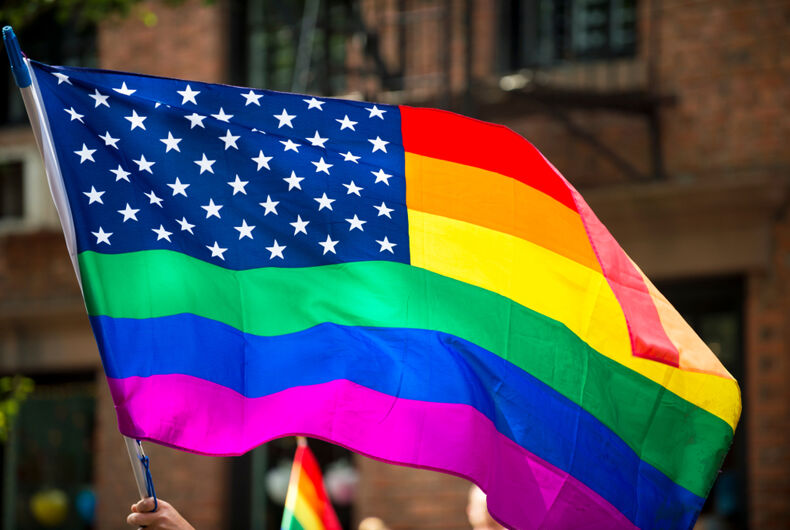 American flag with stars and gay pride rainbow stripes being waved at the annual Gay Pride Parade in Greenwich Village, NYC
