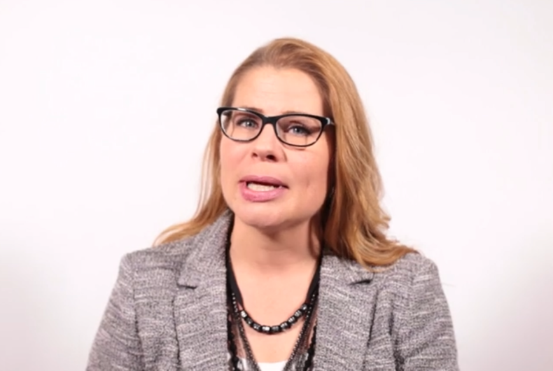 Sarah Parshall Perry, with brunette hair, wearing Black glasses and a grey blazer