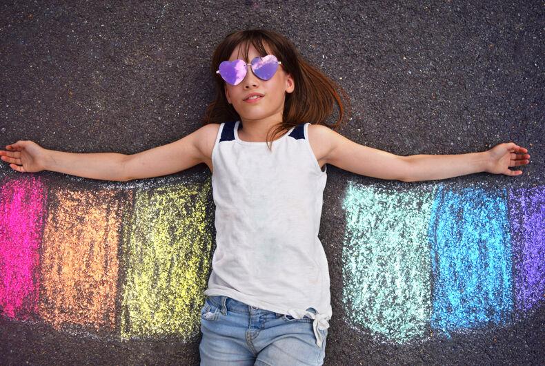 kid with rainbow chalk design
