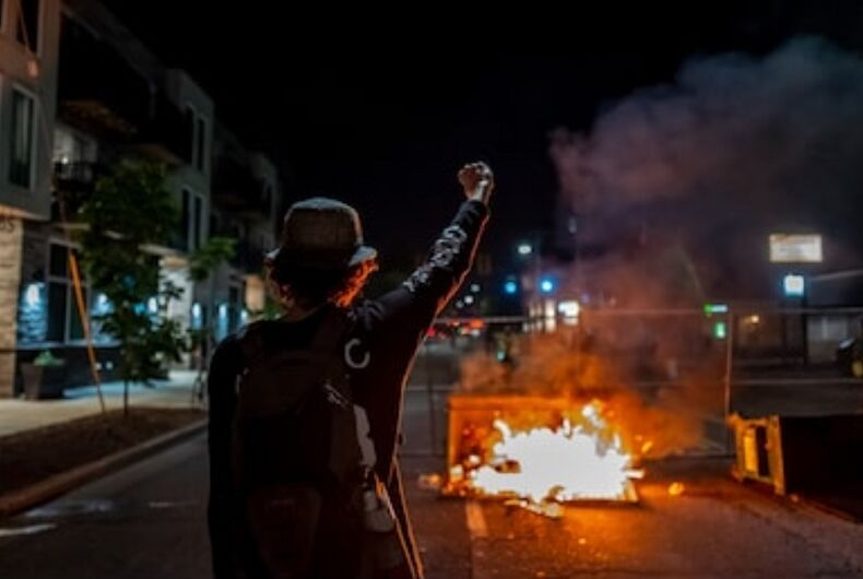 A protestor in Portland, OR raises a fist during nights of anti-fascism and racial injustice protests.