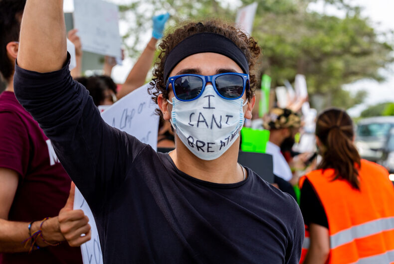 A man wearing sunglasses and a mask with the phrase