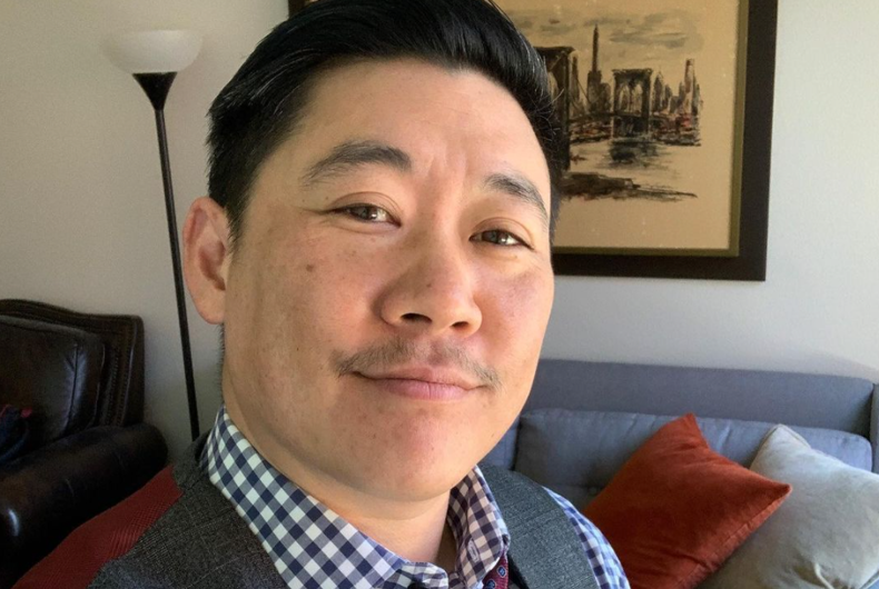 CEO of Sharpe Suiting, Leon Wu, poses in a blue, gray and red suit in his apartment.