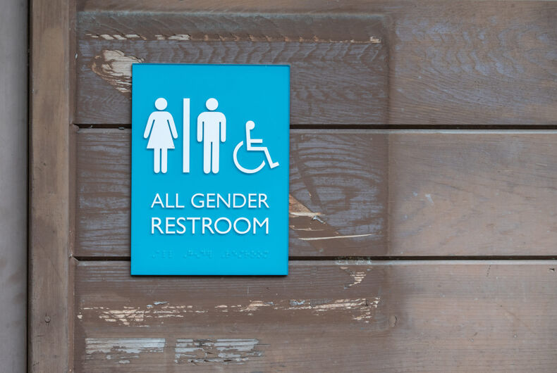 All gender restroom sign with Braille code and wheelchair symbol on the side of a wooden panel wall of building.