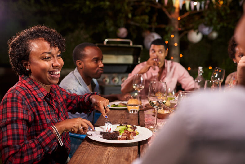 Black Adults enjoying dinner and conversation in garden