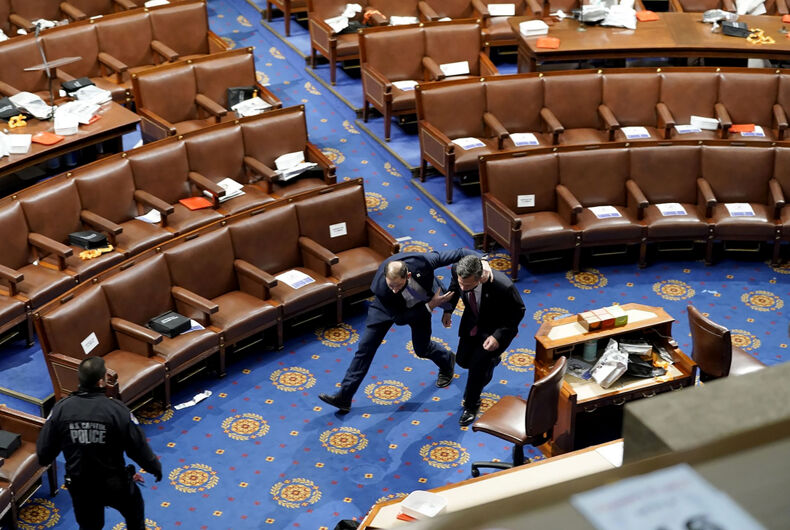 Members of Congress run for cover as protesters try to enter the House Chamber during a joint session of Congress, Washington, D.C., U.S., Jan. 6, 2021.