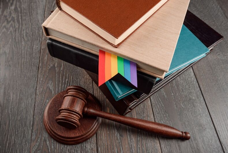A gavel and a rainbow bookmark in a law book