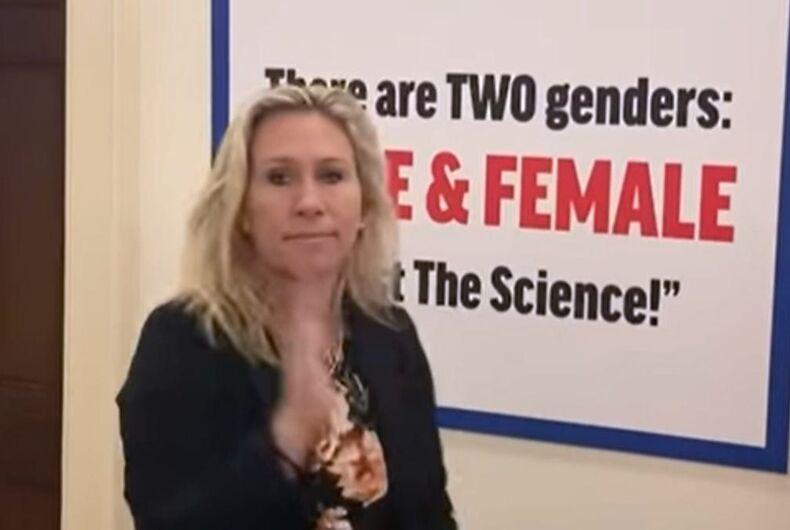 Rep. Marjorie Taylor Greene smirks next to her transphobic sign.