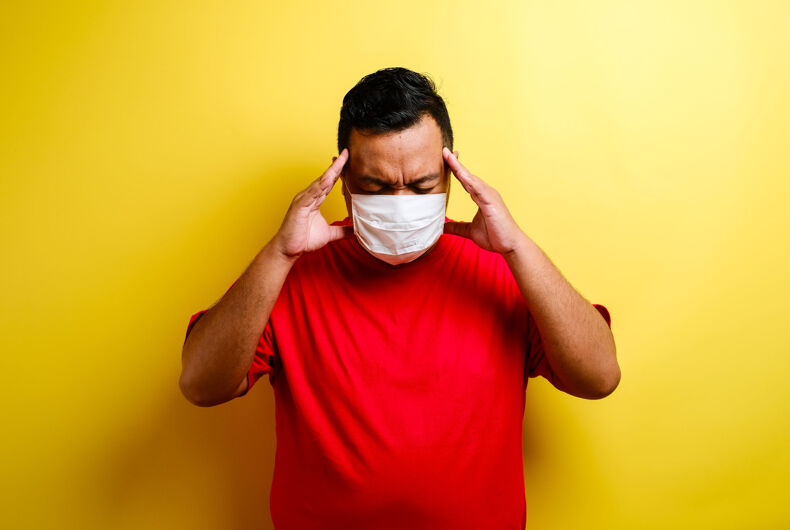 Portrait of young ill man in medical protective mask on face suffering from headache and weakness, isolated on yellow background