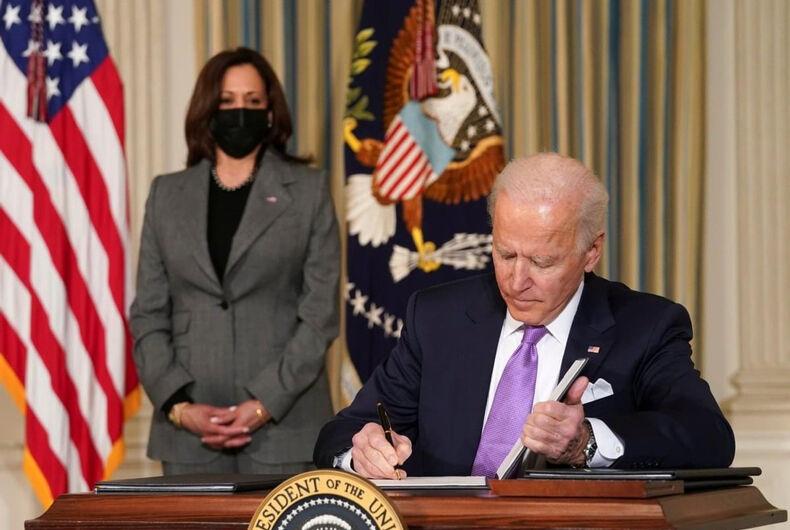 President Joe Biden signing papers in the White House as Vice President Kamala Harris looks on.