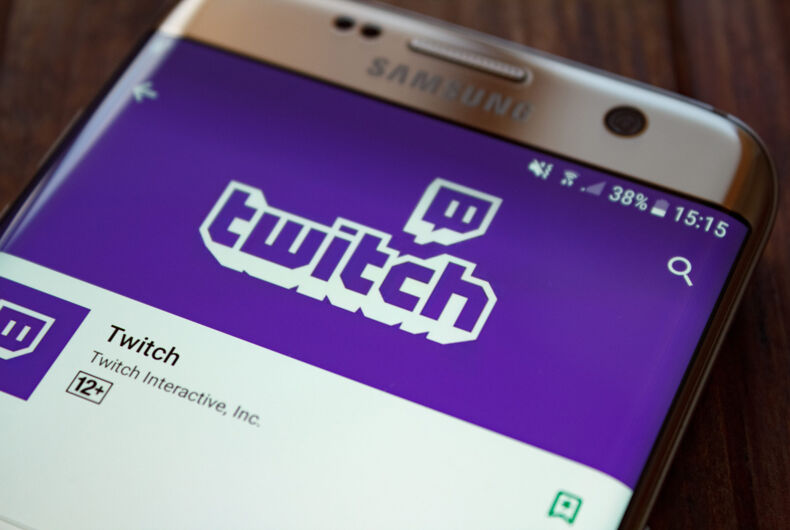 Twitch logo on smartphone screen on wooden background.