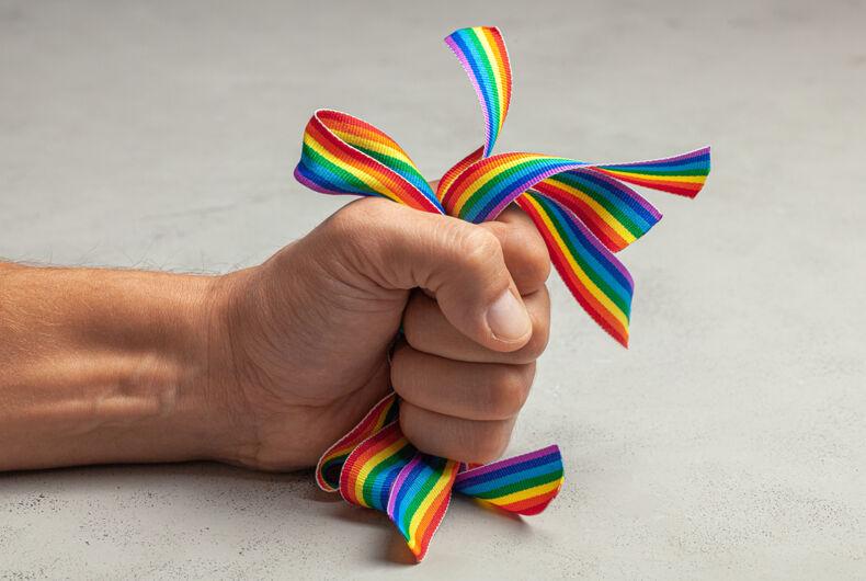 A hand grabbing rainbows tightly
