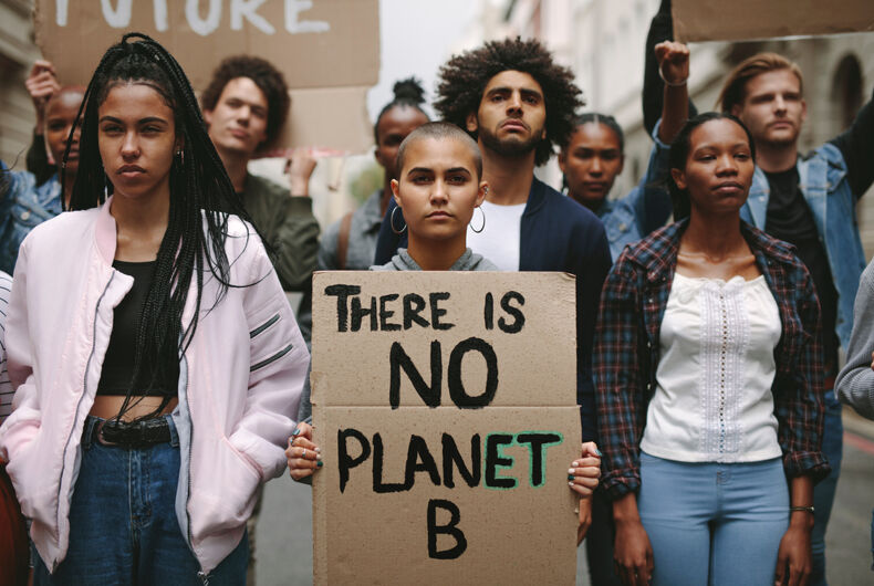 Group of activists with banners protesting over pollution and global warming. Male and female rebellions doing a silent protest to save planet earth. Woman holding a banner of 'There is no Planet B'.