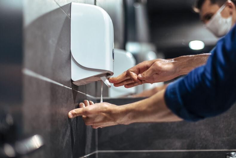 men carefully washes their hands in a restroom