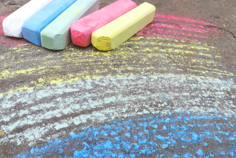 rainbow is drawn with chalk on the asphalt. colored summer background. children drawing, lgbt symbol