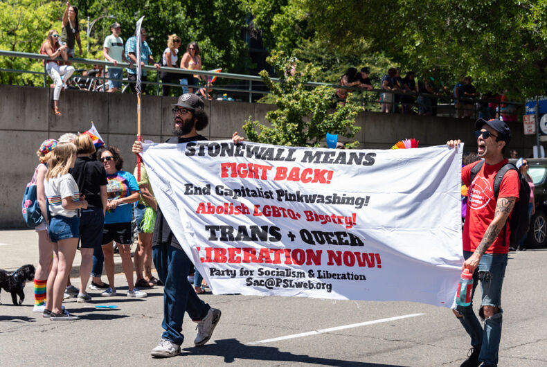SACRAMENTO, CA/U.S.A. - JUNE 10, 2018: Two unidentified men carry a Stonewall banner about fighting back and trans and queer liberation during the annual Pride parade and celebration