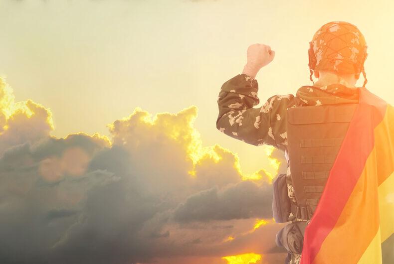 Member of military holding Pride flag under sunset