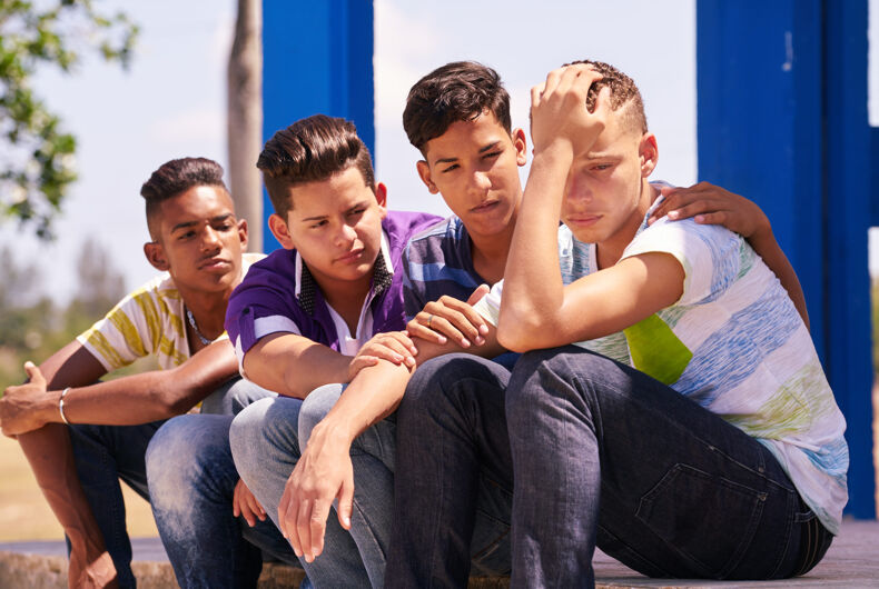 Group of multi-ethnic teens in park. Boys comforting sad friend
