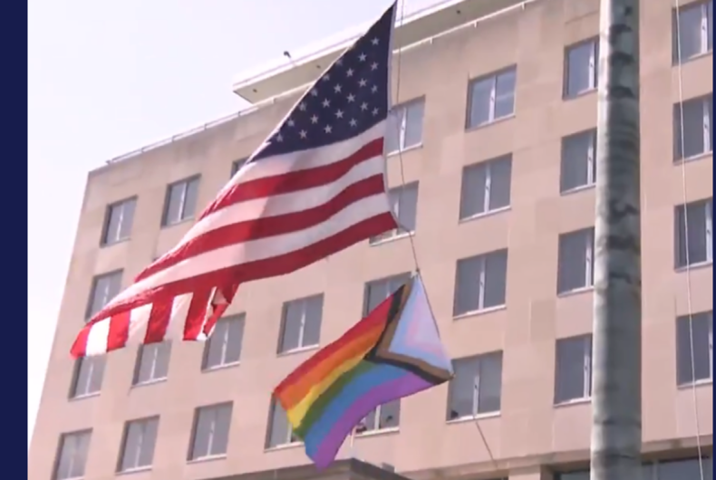 The Progress flag being raised under the American flag outside of the Harry S. Truman Building in Washington, D.C. on June 25, 2021.