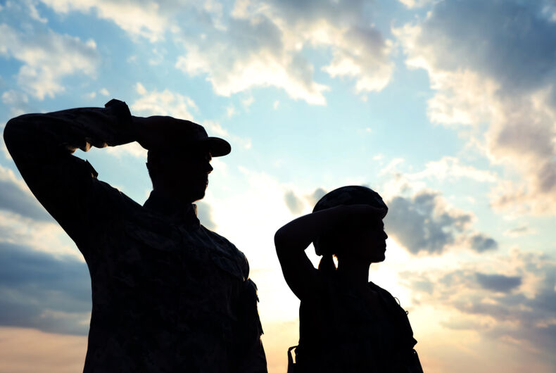 Two silhouettes of people in the military saluting