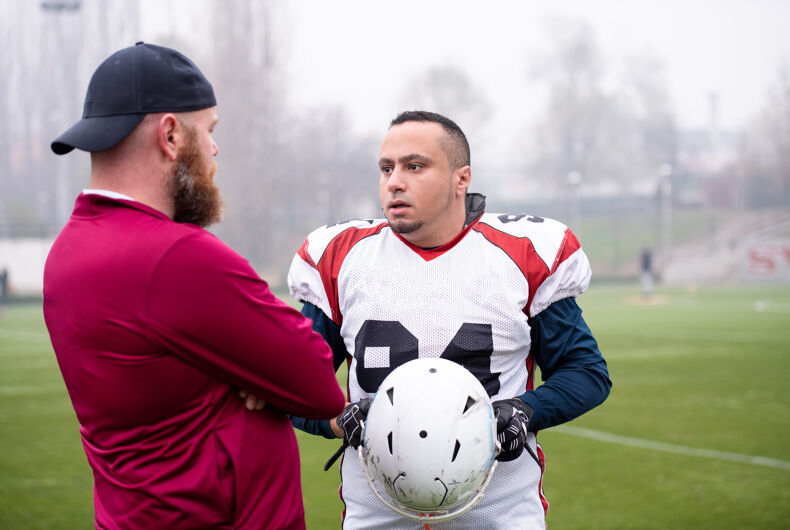 young professional american football player discussing strategy together with coach during training match on the stadium field