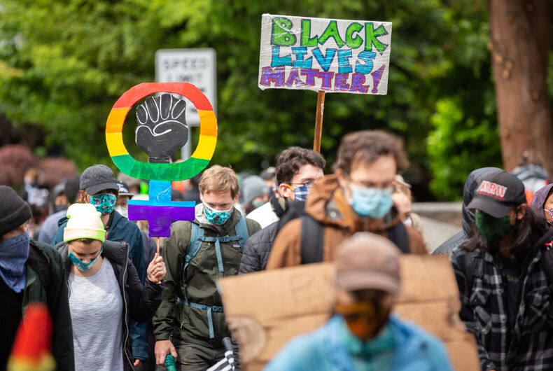 Protester with a rainbow BLM face mask raises a fist in solidarity during the